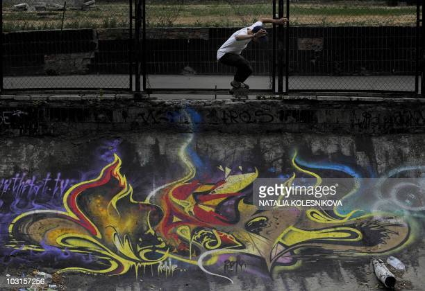 Russian teenager skateboarder rides next to a wall covered in graffiti and street art in Moscow on July 29 2010 AFP PHOTO / NATALIA KOLESNIKOVA