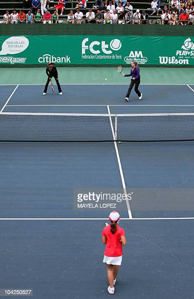 Russian tennis player Anna Kournikova and US tennis player Ashley Harkleroad play with a girl on September 18 in Heredia 18 kilometers north from San...