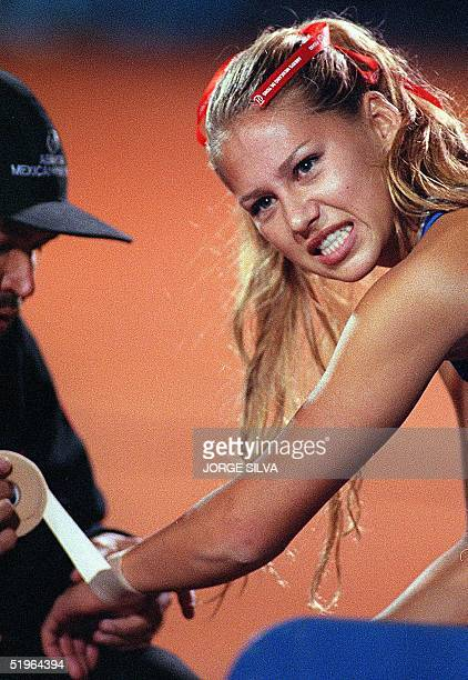 Russian tennis player Anna Kournikova reacts to the pain as a medic wraps up her wrist after she sustained an injury in her women's doubles match...