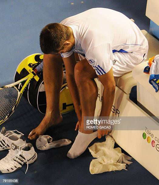 Russian tennis player Mikhail Youzhny adjusts his socks during a break in his mens singles match against French JoWilfried Tsonga at the Australian...