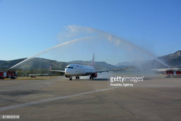 Russian tourists brought with a Boeing 737800 belonging to Royal Flight Airlines Company are given a water cannon salute from fire trucks following...