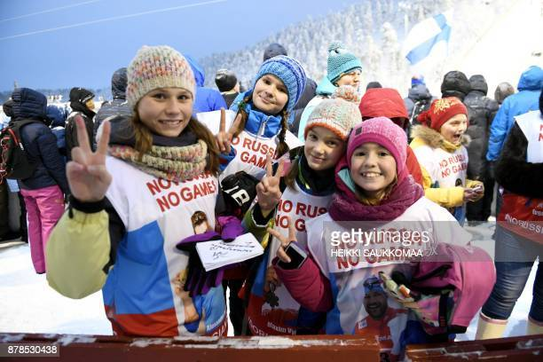 Russian tourists wear 'No Russia No Games' vests during the men's ski jump qualification at the Ruka Nordic World Cup event in Ruka Kuusamo in...