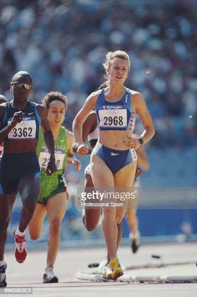 Russian track athlete Olga Raspopova competes alongside Jearl MilesClark of the United States to finish in third place in heat 2 of the first round...