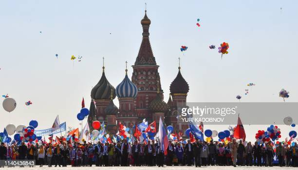 TOPSHOT Russian Trade Unions' members holding balloons flags and artificial flowers parade on Red Square during their May Day demonstration in Moscow...