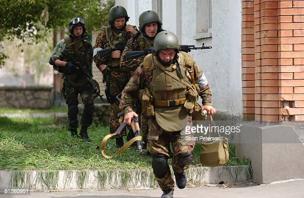 Russian troops run past sniper fire near a school September 3 2004 in Beslan Russia More than 200 people were reportedly killed and at least 700...