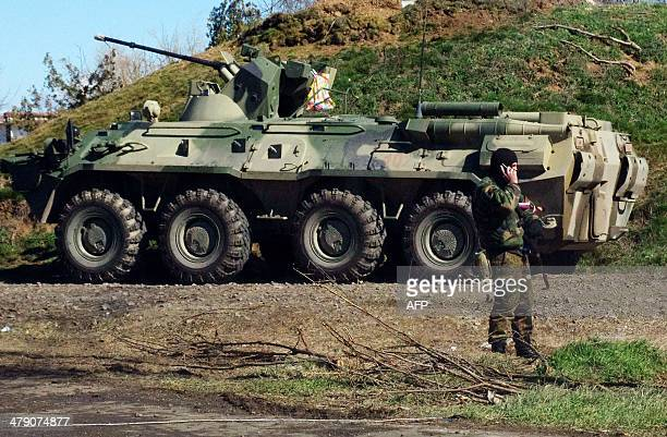 A Russian troops stands guard in front of an APC at a checkpoint in Crimea near the town of Armyansk on March 16 2014 as Crimeans took to the polls...