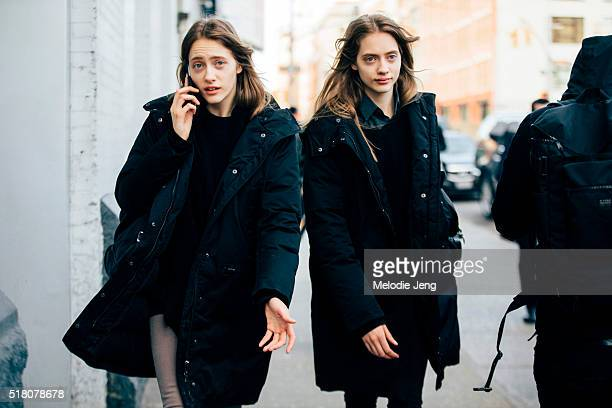 Russian twin models Lia Pavlova and Odette Pavlova exit the Lacoste show and talk on the phone at Spring Studios in black anoraks during New York...