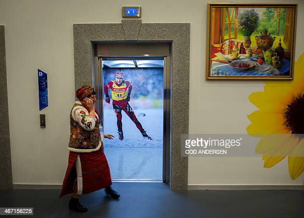 A Russian woman in a traditional dress walks by an elevator where a giant photo of Norway's biathlon champion Ole Einar Bjoerndalen of Norway is...