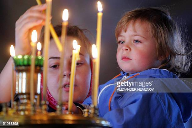 Russian woman lights a candle 05 September 2004 during a memorial service in Moscow for the 394 victims of the threeday school siege in the southern...