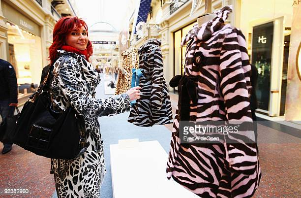 Russian woman looks for a modern coat in the huge famous and exclusive GUM Shopping Mall on the Red Square on October 14 2009 in Moscow Russia Moscow...