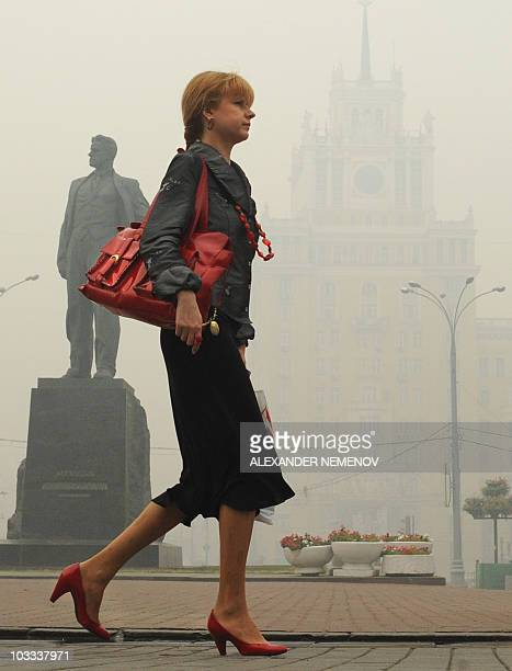 A Russian woman walks past a monument blanketed in forest fire smog in central Moscow on August 6 2010 Smog from wildfires in the countryside cloaked...