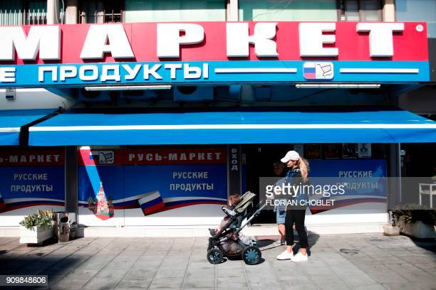 A Russian woman walks past a Russian supermarket in the Cypriot port city of Limassol on January 10 2018 / AFP PHOTO / Florian CHOBLET