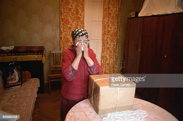 A Russian woman weeps after receiving a package from the Moscow District Council who distributes food to survivors of World War II