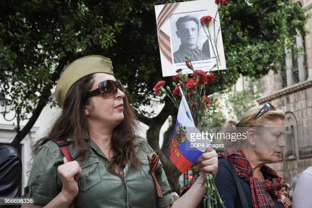 Russian woman who lives in Greece seen holding an old photograph during The Immortal Regiment march Thousands of Russian citizens participated in the...