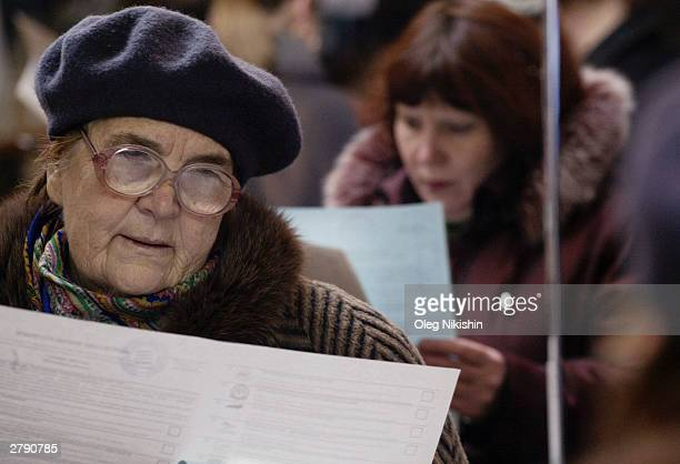 Russian women check their ballot papers before voting in a polling station December 7 2003 in Moscow Russian voters went to the polls to elect a new...