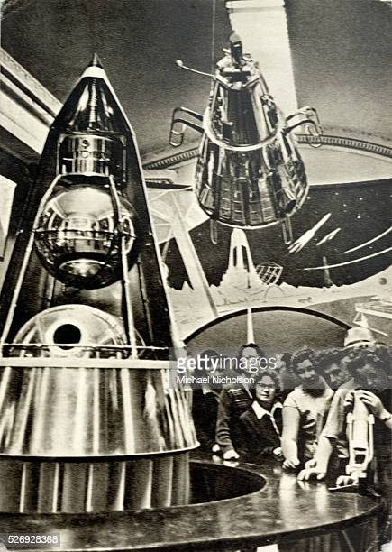Russian women examining a sputnik satellite in the nosecone of a rocket in a museum Above them is another satellite and a fantastic diaroma of outer...
