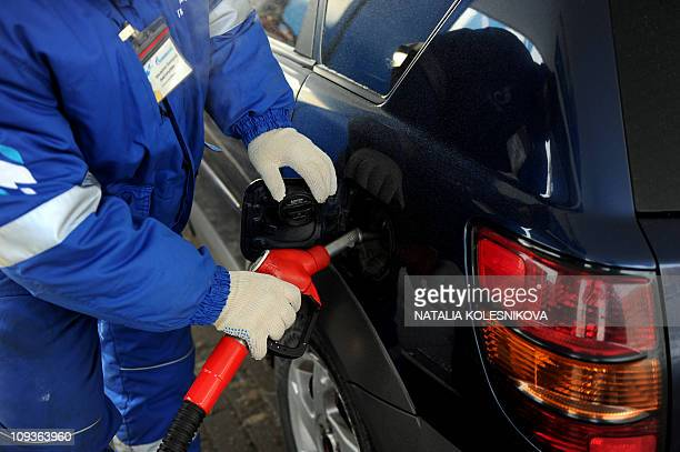 A Russian worker refuels a car at the Gazprom Neft gas station in Moscow on February 17 2011 AFP PHOTO / NATALIA KOLESNIKOVA