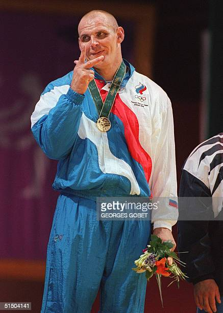 Russian wrestler Alexander Karelin shows three fingers after winning his third gold medal on the podium of the super heavyweight Grecoroman final 24...