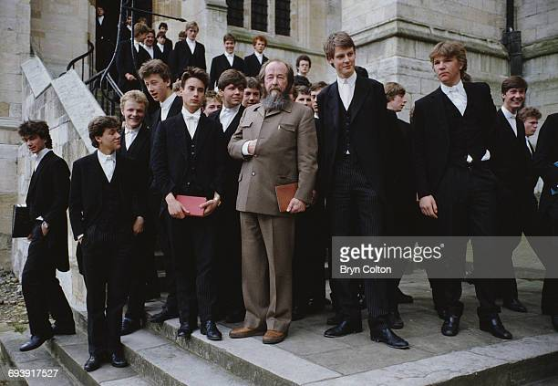 Russian writer Aleksander Isayevich Solzhenitsyn centre stops to pose for a photograph with pupils outside Eton College Chapel the boys all dressed...