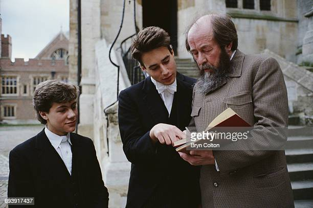Russian writer Aleksander Isayevich Solzhenitsyn stops to sign his autograph and talk to pupils outside Eton College Chapel the boys all dressed in...