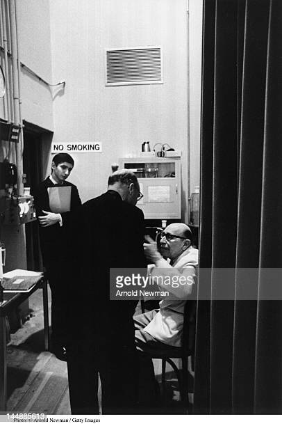 Russian-American composer Igor Stravinsky speaks with an unidentified man backstage as sixteen-year-old pianist and future conductor Michael Tilson...