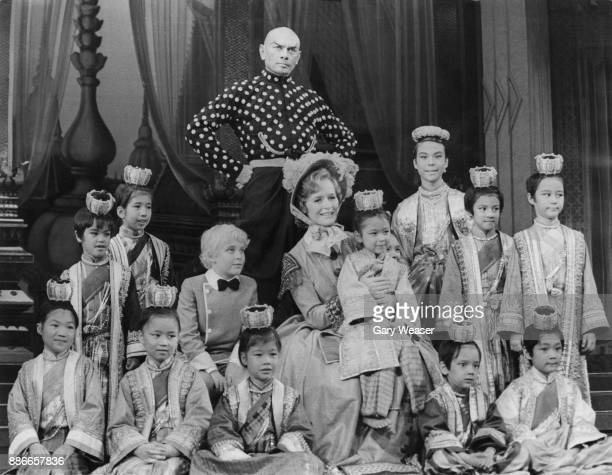 Russianborn actor Yul Brynner and actress Virginia McKenna with young cast members during a photocall for the play 'The King and I' at the London...