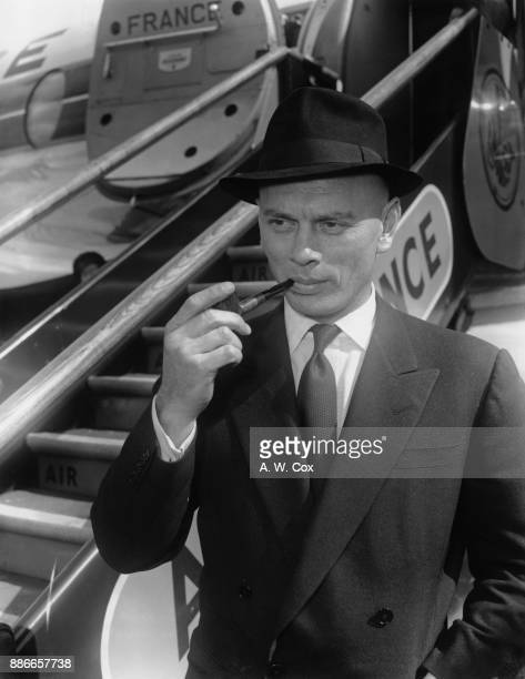 Russianborn actor Yul Brynner leaves London Airport for Paris via Air France with one of the pipes which he bought in London 9th May 1957