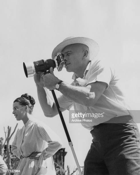 Russianborn actor Yul Brynner uses his camera on the set of the MGM film 'The Brothers Karamazov' 1957 On the left is his costar actress Claire Bloom