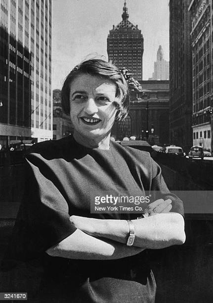 Russianborn American author and philosopher Ayn Rand smiles and stands outdoors with her arms folded in front of the Grand Central building midtown...
