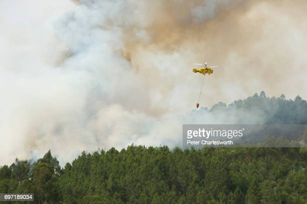 Russianbuilt Kamov KA32 firefighting helicopter drops water on a forest fire above the small village hamlet of Casal de São João Portugal is enduring...
