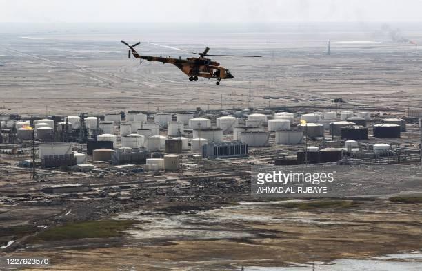 Russian-made Iraqi Mil Mi-17 flies over an oil field near Iraq's southern port city of Basra on July 15, 2020.