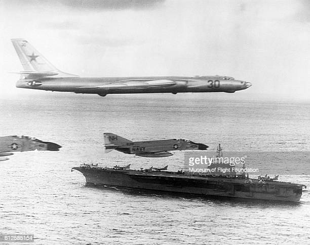 Russian-made Tupolev TU-16 Badger-A surveillance bomber flies with U. S. Navy escort fighters over the attack carrier USS Kitty Hawk during Cold War...