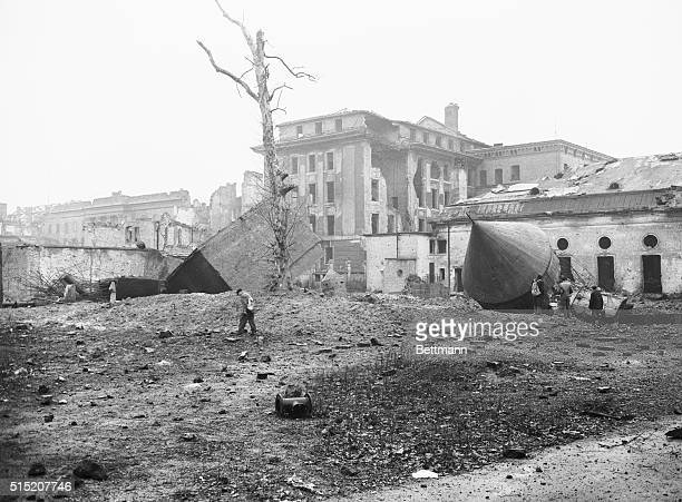 "Russians Blow up Hitler's ""Tombstone."" Berlin, Germany: Sightseers walk amid the ruins of Hitler's air raid shelter, sometimes referred to as..."