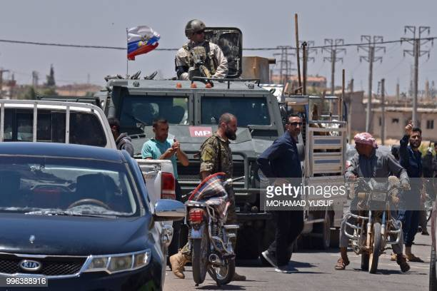 Russians forces are seen as displaced Syrians from the Daraa province come back to their hometown in Bosra, southwestern Syria, on July 11, 2018. -...