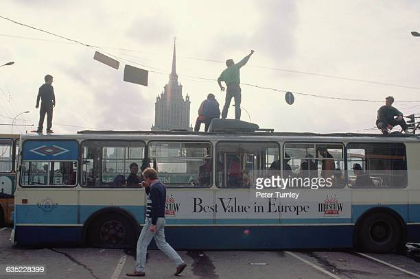 Russians stand on top of buses that are being used as barricades to block access to Red Square.