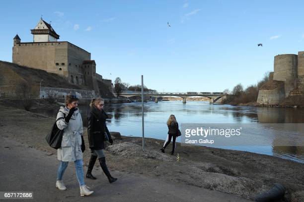 Russianspeaking people walk along a promenade along the Narva River below Hermann Castle and opposite Ivangorod Fortress which is on the Russian side...