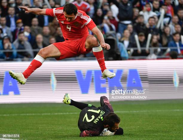 Russia's Alan Dzagoev jumps over Turkey's goalkeeper Serkan Kirintili during an international friendly football match between Russia and Turkey at...