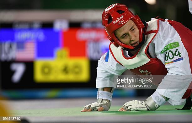 Russia's Albert Gaun falls to the mat during his men's taekwondo qualifying bout agaisnt the USA's Steven Lopez in the 80kg category as part of the...