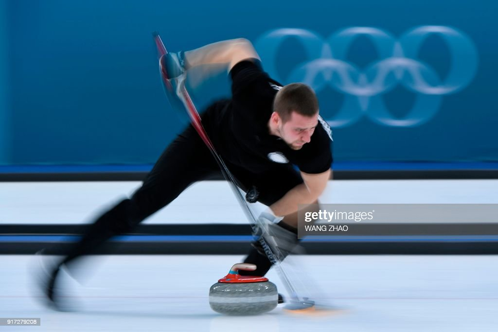 TOPSHOT - Russia's Aleksandr Krushelnitckii brushes in front of the stone during the curling mixed doubles semi-final during the Pyeongchang 2018 Winter Olympic Games at the Gangneung Curling Centre in Gangneung on February 12, 2018. / AFP PHOTO / WANG Zhao