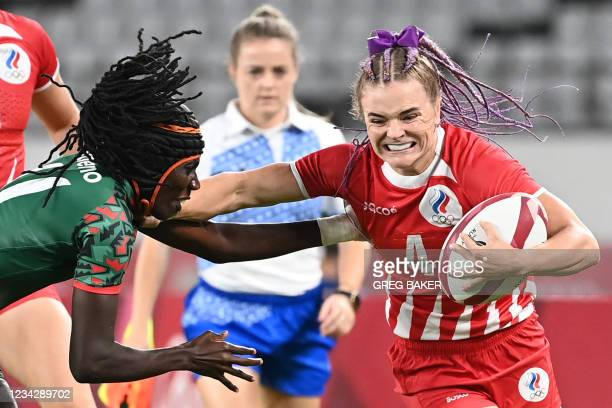 Russia's Alena Tiron fends off a tackle by Kenya's Camilla Atieno during the women's pool A rugby sevens match between the Russia and Kenya during...