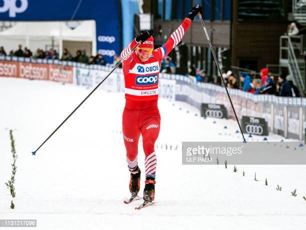 Russia's Alexander Bolshunov crosses the finish line to win the men's 15 km Interval start free style event at the FIS cross country World Cup in...