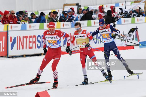 Russia's Alexander Bolshunov Norway's Sjur Roethe and Finland's Matti Heikkinen compete during the Men's cross country skiing relay 4x10km event at...