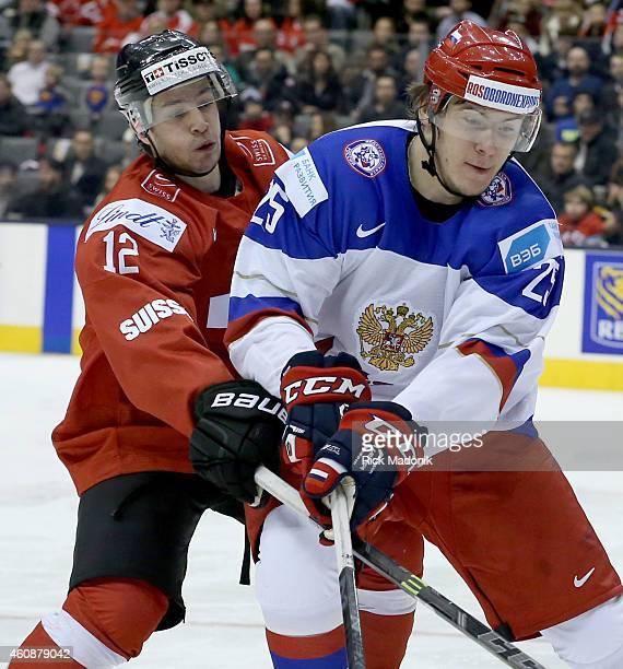 TORONTO DECEMBER 28 Russia's Alexander Dergachyov is checked by Swiss player Jason Fuchs 2015 IIHF World Junior Championship hockey Russia vs...