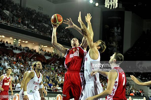 Russia's Alexander Kaun jumps to score as Turkey's Semih Erden tries to stop him during their World Championship preliminary round basketball game in...