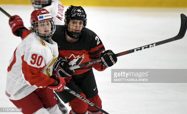 Russia's Alexandra Vafina and Canada's Emily Clark battle during the IIHF Women's Ice Hockey World Championships bronze medal match between Canada...