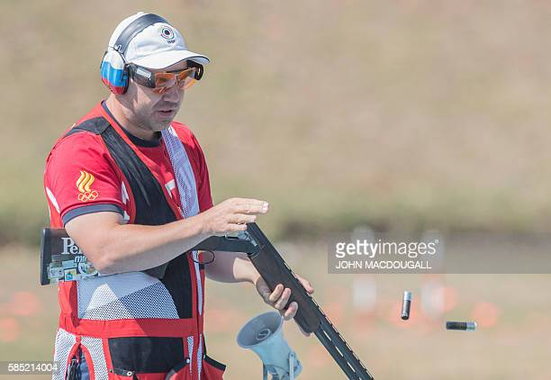 Russia's Alexey Alipov throws empty cartridges away as he trains for the trap shooting event at the Olympic Shooting Centre in Rio de Janeiro on...