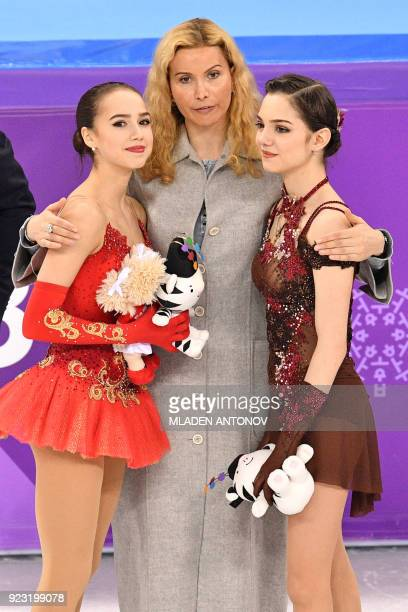 Russia's Alina Zagitova and Russia's Evgenia Medvedeva pose with their coach after their respective gold and silver wins following the venue ceremony...