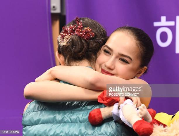 Russia's Alina Zagitova hugs Russia's Evgenia Medvedeva after the women's single skating free skating of the figure skating event during the...