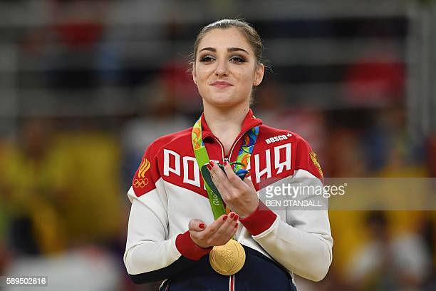 Russia's Aliya Mustafina celebrates on the podium of the women's uneven bars event final of the Artistic Gymnastics at the Olympic Arena during the...