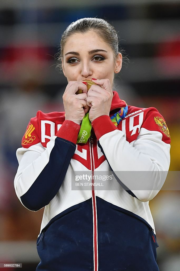 Russia's Aliya Mustafina celebrates with her gold medal on the podium of the women's uneven bars event final of the Artistic Gymnastics at the Olympic Arena during the Rio 2016 Olympic Games in Rio de Janeiro on August 14, 2016. / AFP / Ben STANSALL
